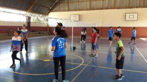 Alunos do projeto Vôlei em Rede auxiliam convidados durante atividades.